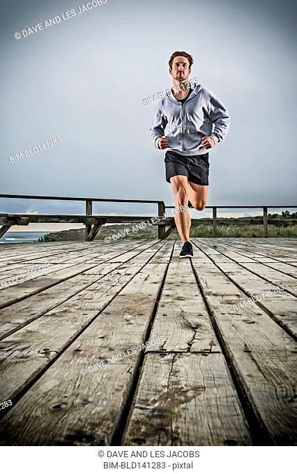 Caucasian man running on wooden boardwalk
