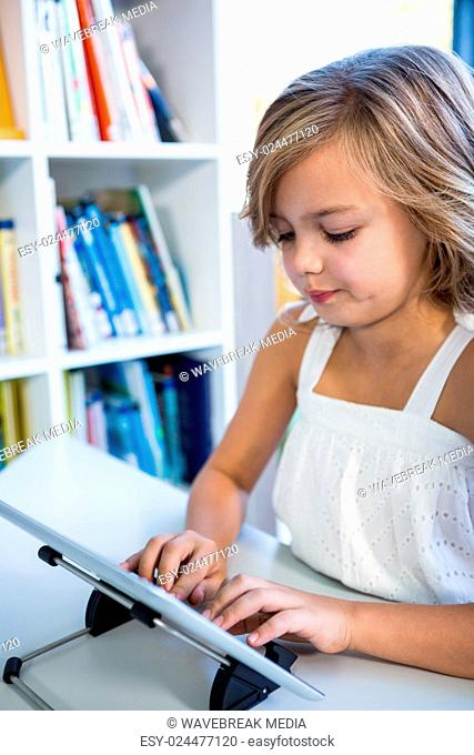 Elementary girl using digital tablet in library