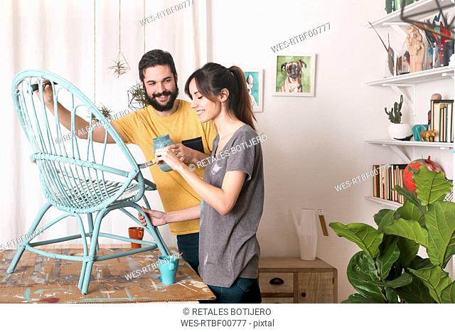 Young couple painting wicker armchair in blue at home