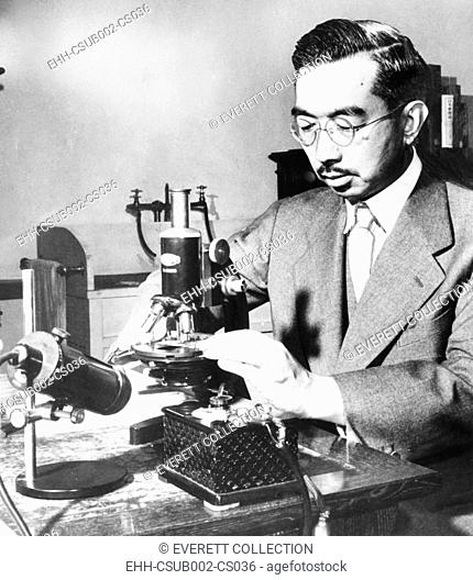 Emperor Hirohito puts specimens on a slide under the microscope in his marine biology laboratory. July 31, 1954. Since childhood, he pursued biology