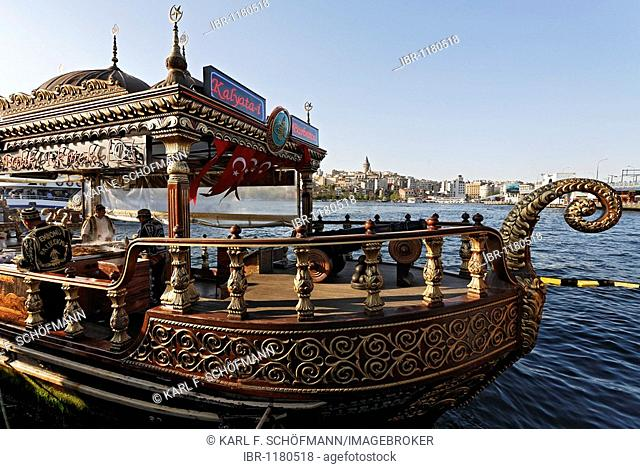 Fish diner with fish sandwiches for sale on a richly decorated golden boot, Golden Horn, Eminoenue, Istanbul, Turkey