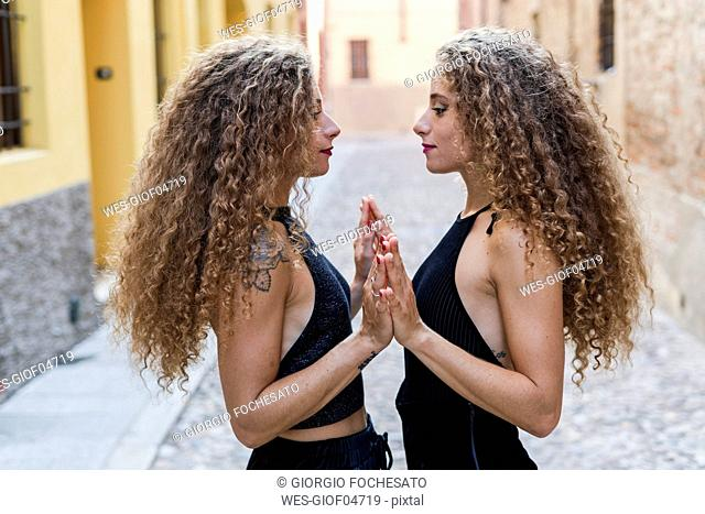 Side view of twin sisters standing face to face touching hands
