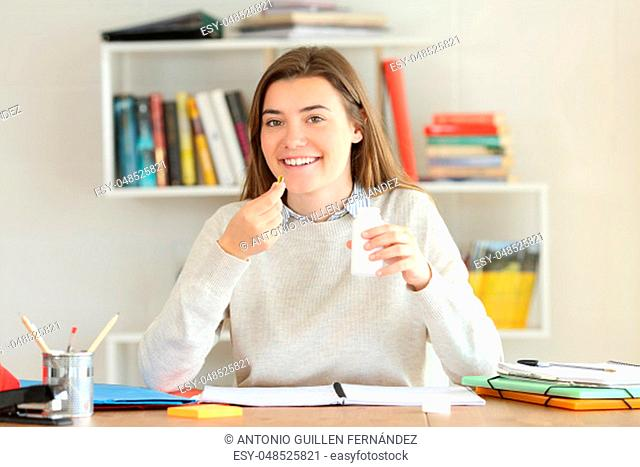 Front view portrait of a happy student holding vitamin supplement pills at home