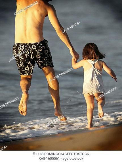 FATHER AND DAUGHTER PLAYING ON THE BEACH IN GALICIA SPAIN VALDOVIÑO