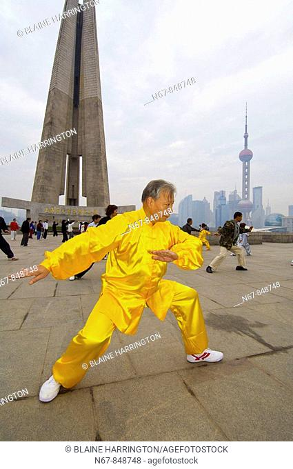 Chinese people practicing tai chi in the early morning in Huangpu Park with the Monument to the People's Heroes in the background, Shanghai, China