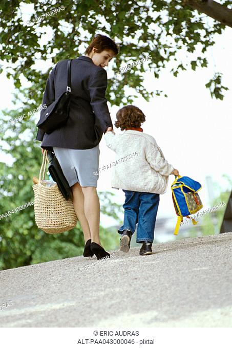 Businesswoman and child holding hands, walking, rear view