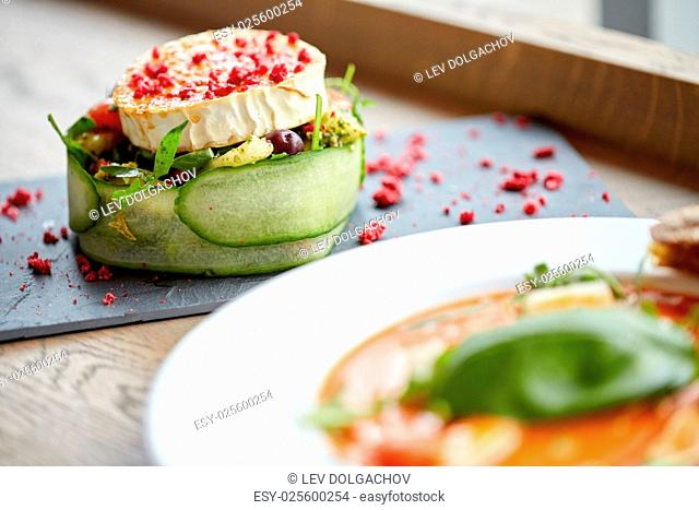 food, culinary, haute cuisine and cooking concept - goat cheese salad with vegetables and dried raspberries at restaurant or cafe