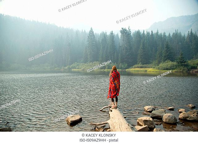 Woman wrapped in tartan blanket looking out over misty lake, Mount Hood National Forest, Oregon, USA