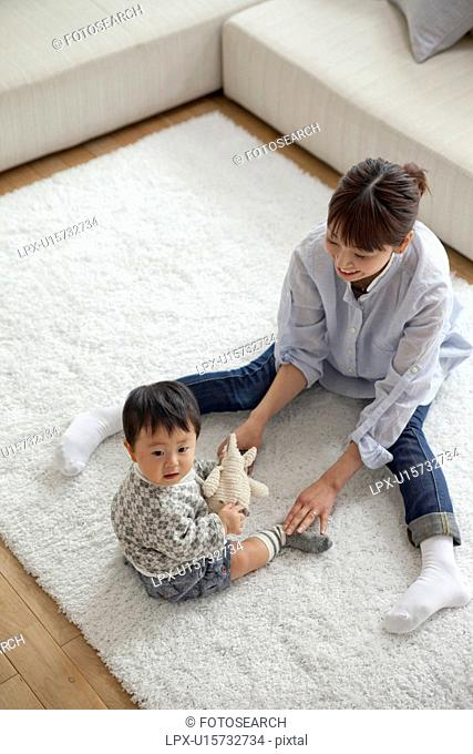Mother and baby boy playing in living room