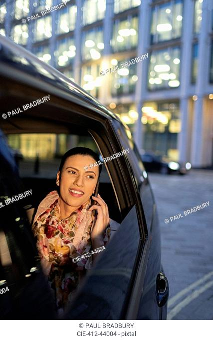Smiling businesswoman talking on smart phone in crowdsourced taxi at night