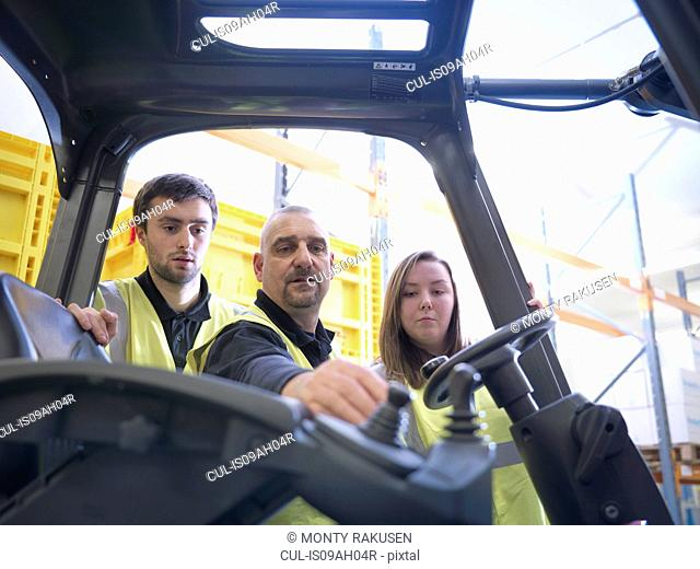 Instructor showing apprentices controls of forklift truck