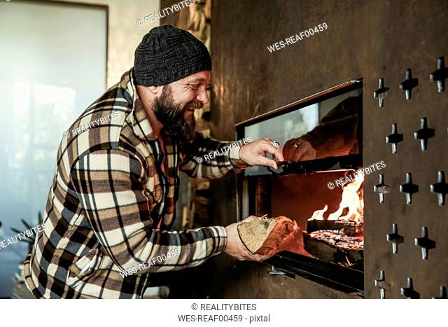 Happy bearded man in front of fireplace at home