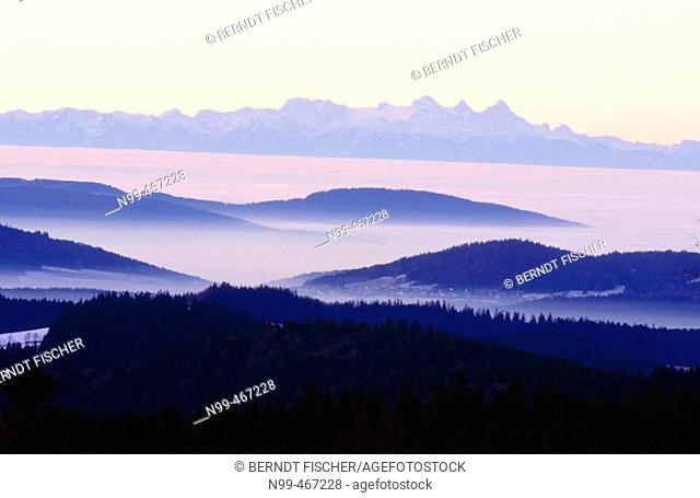 Inversion weather fog in the valleys wooded mountains in the foreground. National Park Bavarian Forest to the Chain of Alps. Germany