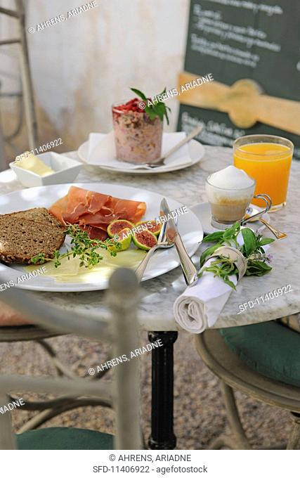 A bistro table table laid with bread, ham, drinks and dessert