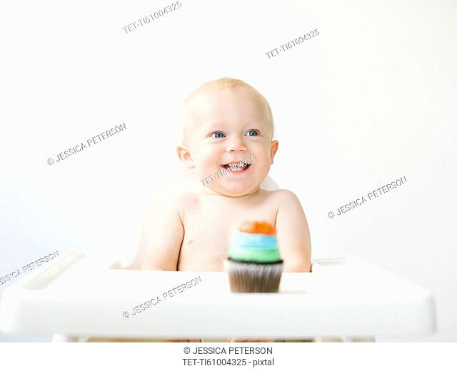 Baby boy (12-17 months) sitting in high chair with cupcake in front of him