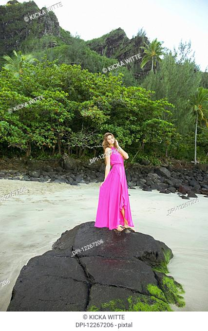 Woman standing on a large rock on the beach; Kauai, Hawaii, United States of America