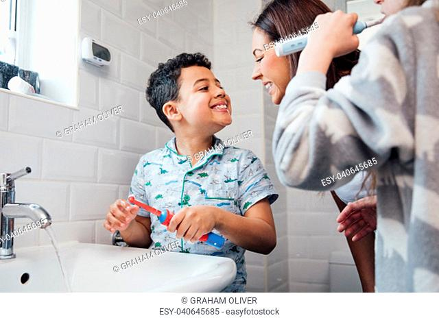 Children are brushing their teeth in the bathroom at home. The mother is checking the little boy's mouth to make sure he has brushed properly
