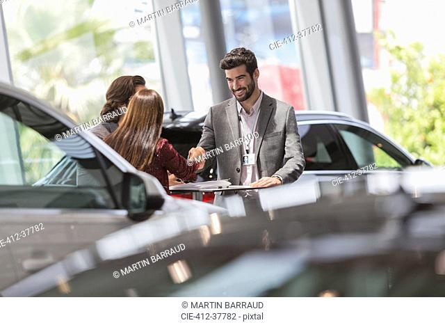 Car salesman handshaking with customers in car dealership showroom