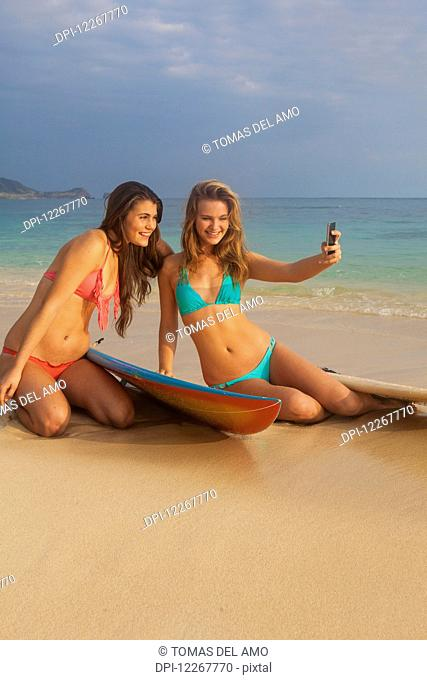Teenage sisters at the beach with cell phone; Kailua, Island of Hawaii, Hawaii, United States of America