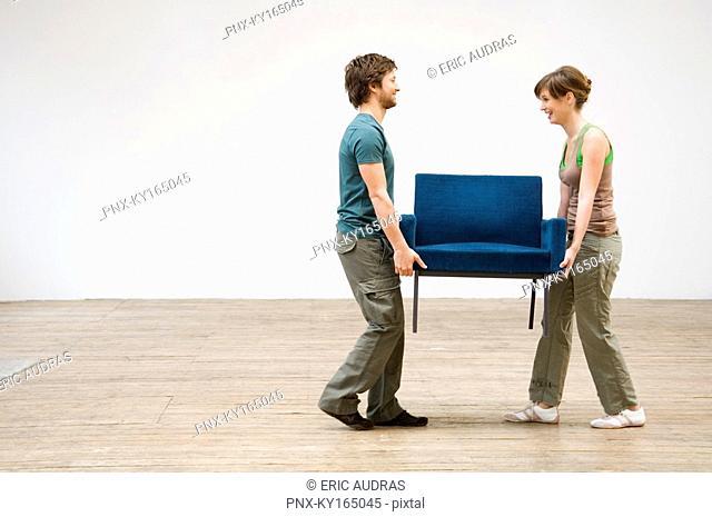 Couple carrying an armchair