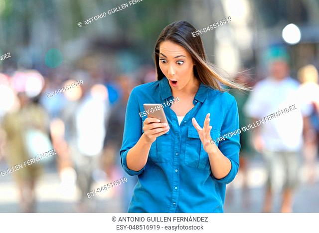 Shocked woman reading smart phone messages walking on the street