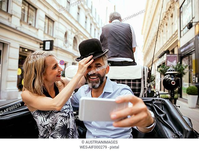 Austria, Vienna, couple having fun on sightseeing tour in a fiaker