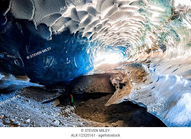 A man stands inside a cavernous ice cave within Canwell Glacier in the Alaska Range in winter, Interior Alaska, USA