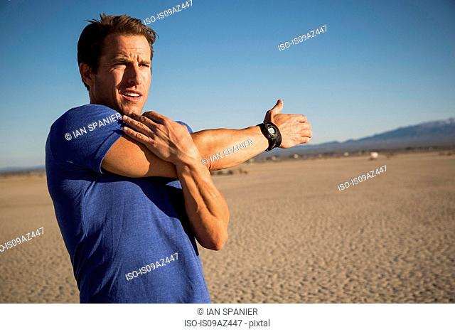 Man training, stretching arms and shoulder on dry lake bed, El Mirage, California, USA