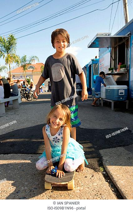 Portrait of young boy and girl on skateboard