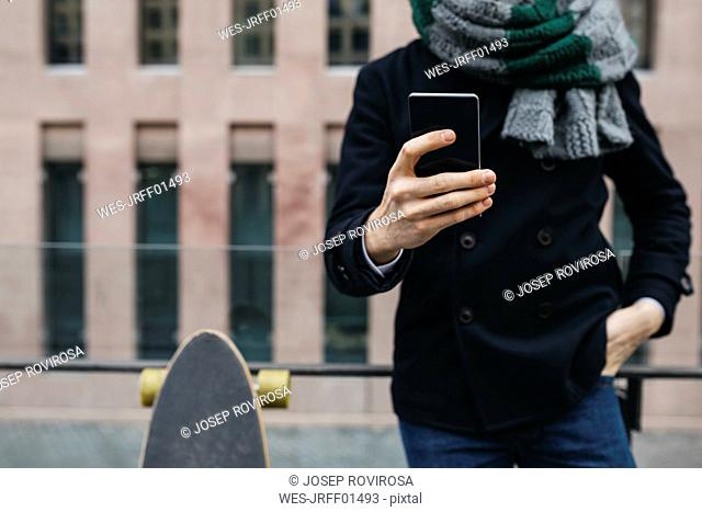Man with cell phone and skateboard in the city, partial view