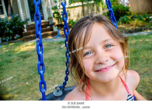 Portrait of cute girl playing on swing in garden