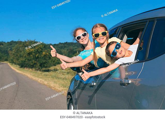 Happy brother and his two sisters are sitting in the car at the day time. They look out the window. Children having fun outdoors