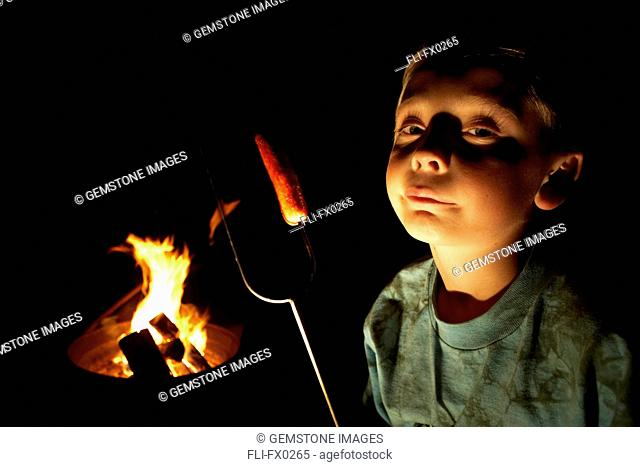 Boy with Hot Dog on Roasting Stick next to Fire, British Columbia