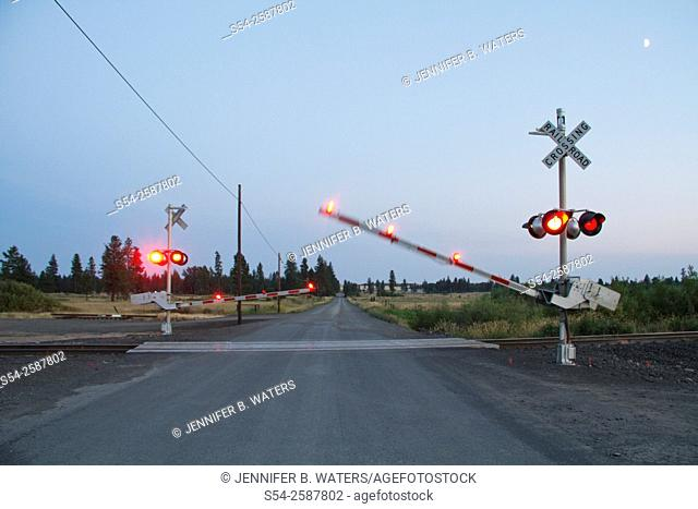 The crossing arms go down at a rural road in Cheney, Washington, USA