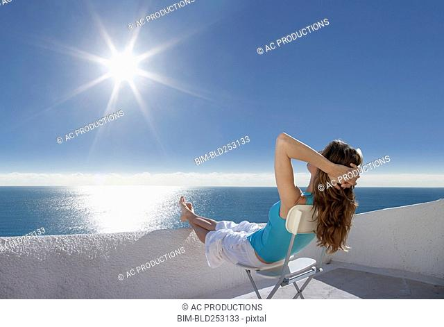Caucasian woman relaxing in chair at ocean