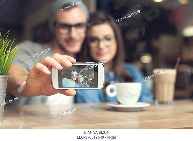 Hipster couple taking selfie at cafe. Krakow, Poland