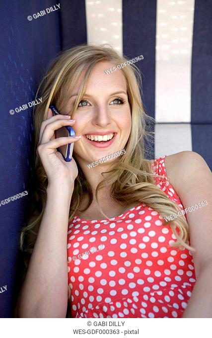 Portrait of smiling young woman telephoning with smartphone