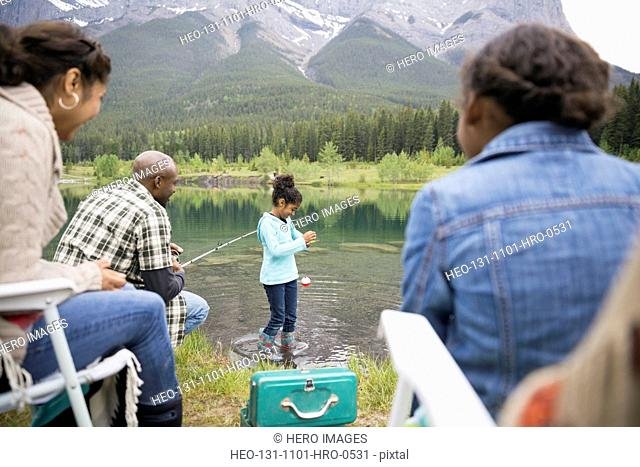 Family fishing at lakeside below mountains