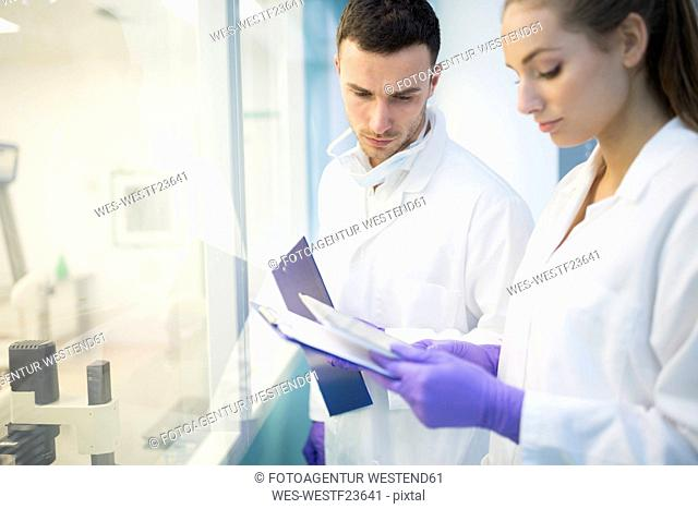 Man and woman in lab coats with clipboards