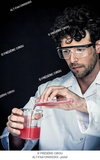 Chemist pouring liquid from test tube into beaker