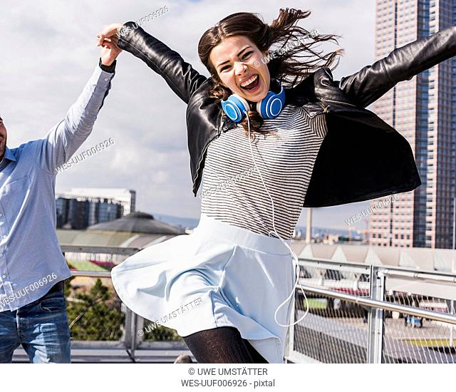 Young happy woman jumping and holding hands with friend