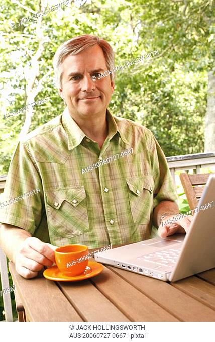 Portrait of a mature man using a laptop and holding a cup