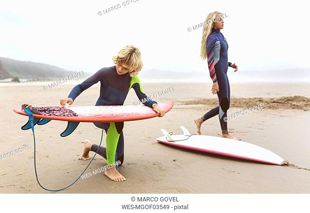 Spain, Aviles, two young surfers on the beach preparing their surfboards