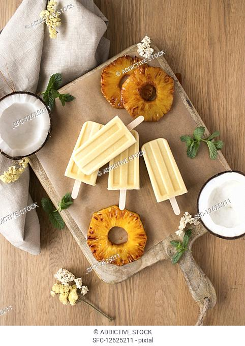 Slices of fresh pineapple, halves of ripe coconut with mint and delicious ice cream on board