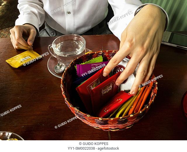 Tilburg, Netherlands. Left hand of an adult caucasian woman grabbing into a basket of tea choosing her blend and flavour