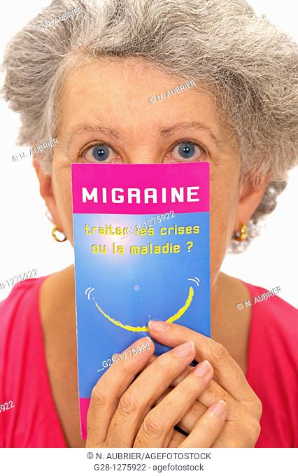 senior woman in pink, suffering from a headache and holding a medical leaflet on headache migraine