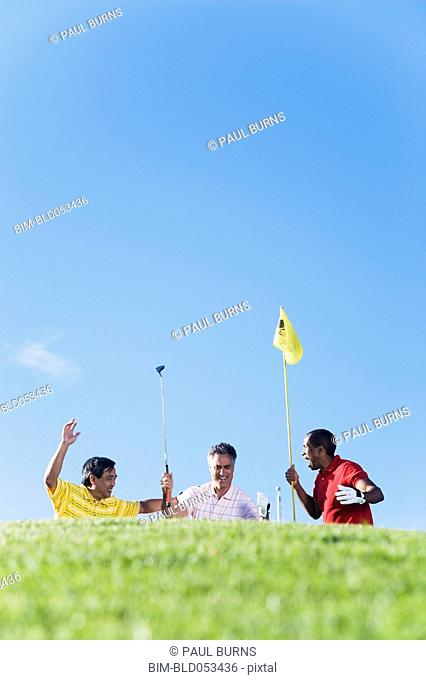 Multi-ethnic men cheering on golf course