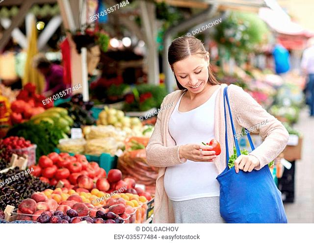 sale, shopping, food, pregnancy and people concept - happy pregnant woman buying red pepper or paprika at street market