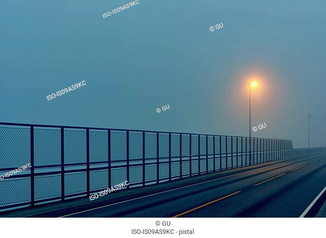 Empty road and safety barrier illuminated by street light, Haugesund, Rogaland County, Norway