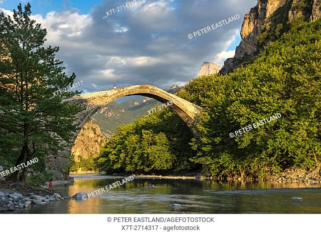The old stone bridge across the Aoos river at Konitsa with Mount Tymfi in the background, Epirus, Northern Greece
